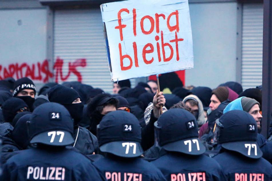 """Polizeibeamte und Demonstranten vor dem Kulturzentrum """"Rote Flora"""" im Schanzenviertel."""