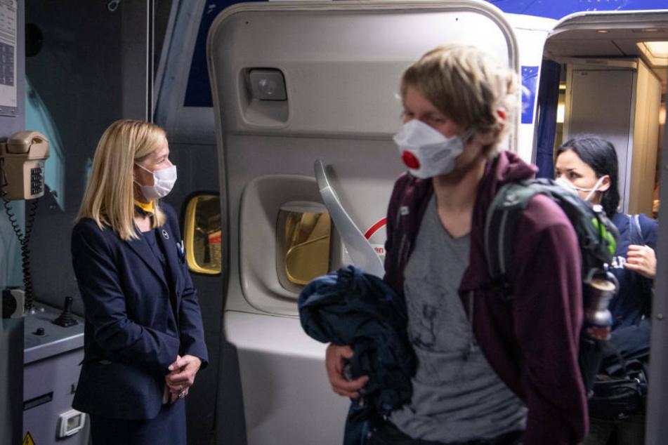 Eine Flugbegleiterin mit Mundschutz begrüßt Passagiere einer Boeing 747 der Lufthansa nach ihrer Landung auf dem Flughafen Frankfurt.