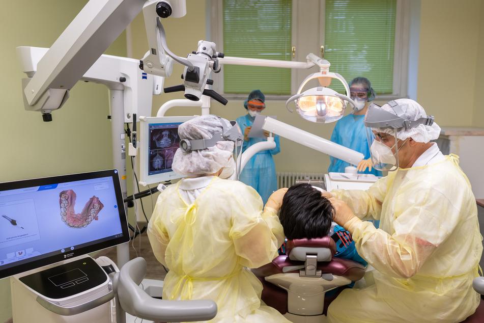 Ein Zahnarzt behandelt mit Visier, FFP3-Atemschutzmaske und Virenschutzkittel mit seinen Zahnmedizinischen Fachangestellten einen Corona-Patienten in seiner Dresdner (Sachsen) Zahnarztpraxis.