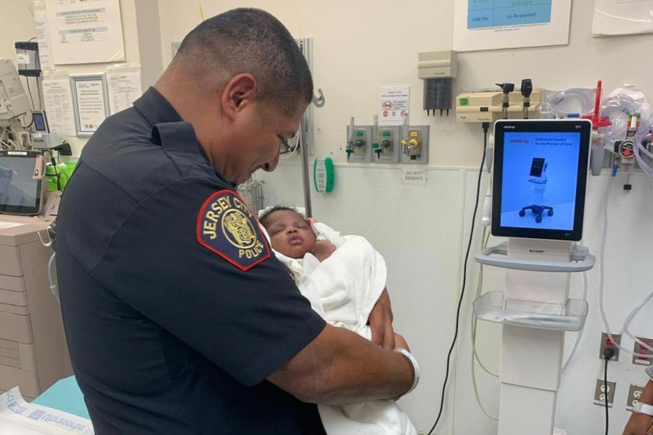 Der Polizist Eduardo Matute hält im Krankenhaus das Kind in den Händen, dessen Leben er zuvor mit einer heldenhaften Reaktion gerettet hat.