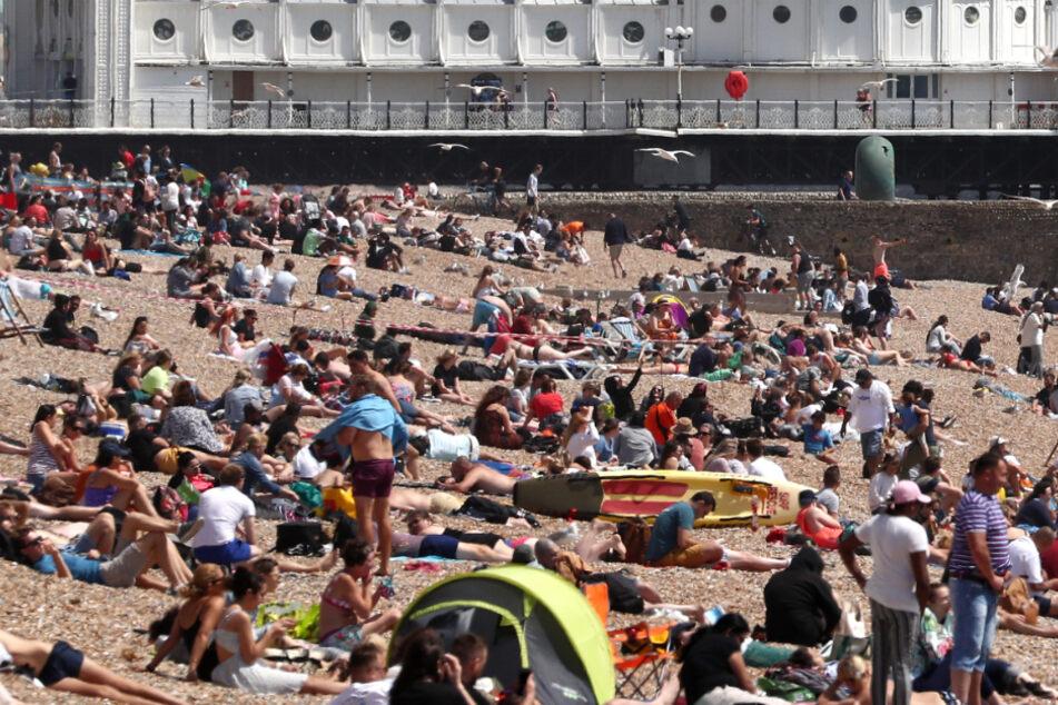 Die Menschen genießen das Wetter am Strand am Brighton Palace Pier.