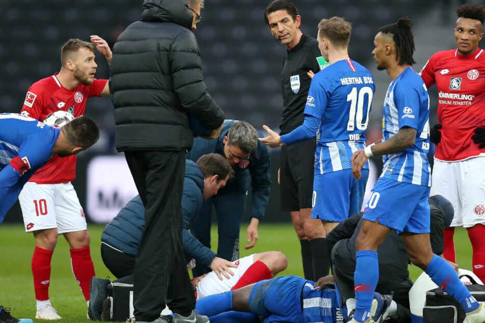 Nach Zusammenstoß liegen Jordan Torunarigha von Hertha BSC (r) und Stefan Bell von Mainz 05 verletzt am Boden.