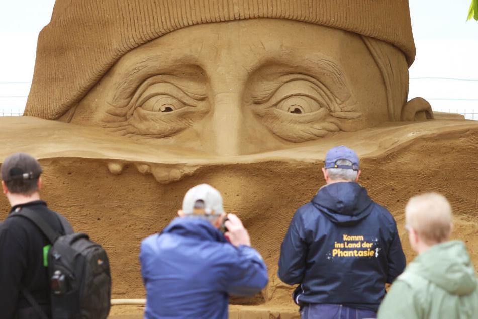 """Besucher betrachten die Skulptur """"Auf der Suche nach Atlantis"""" am Passagierkai in Warnemünde."""
