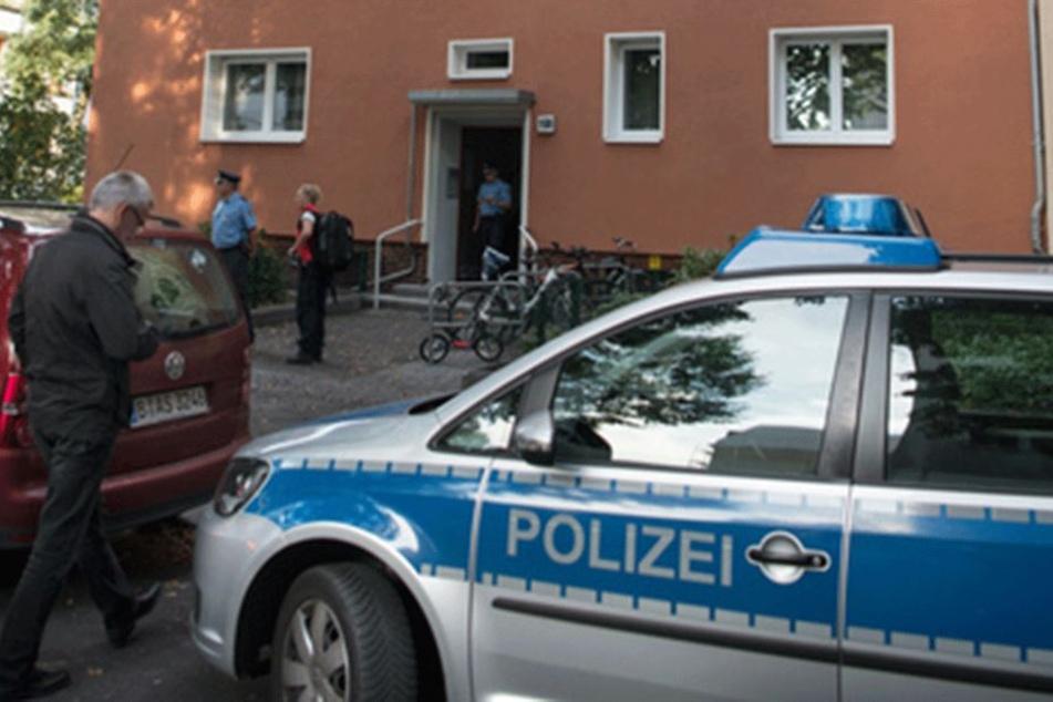 Polizisten stehen vor dem Haus, in dem die zwei Leichen gefunden wurden.