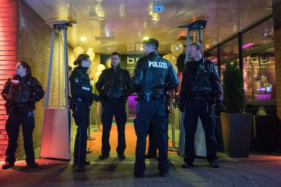 Die Beamten stehen vor dem Eingang des Nachtclubs.