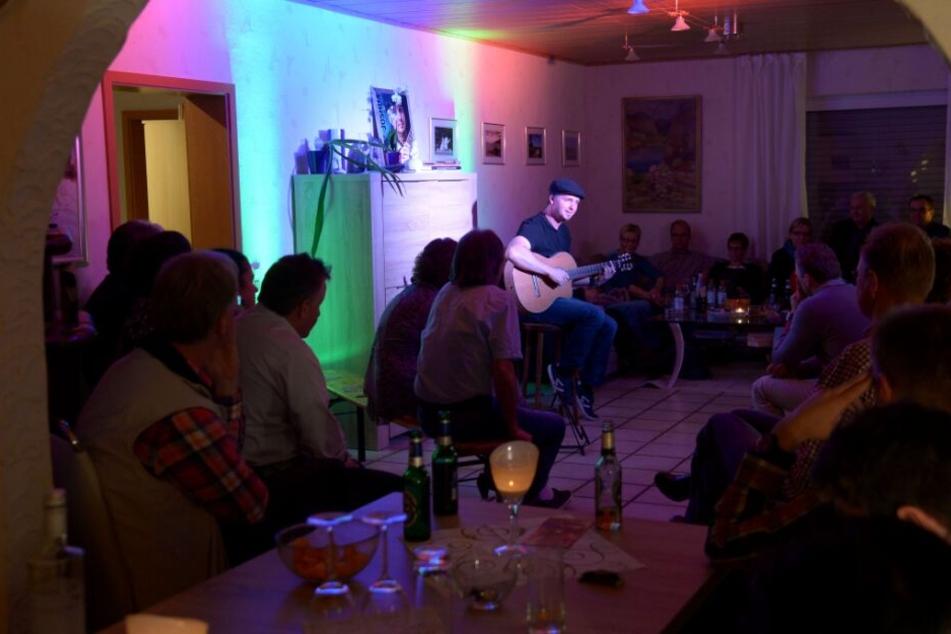 Der Musiker Joshua Carson tritt in einem fremden Wohnzimmer auf.