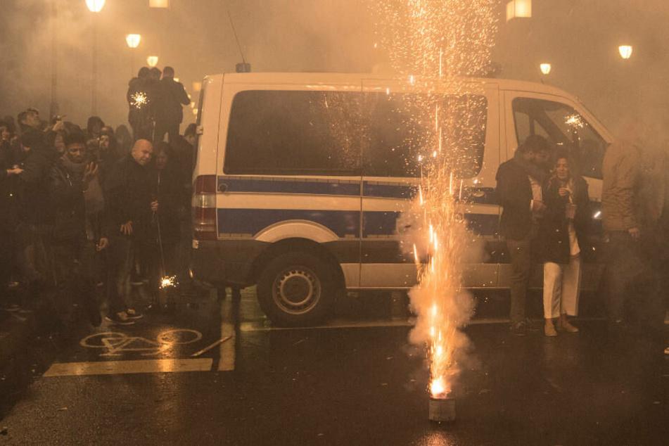 Vor einem Polizeiwagen wird Feuerwerk gezündet: Bild aus der Silvesternacht 2019 in Frankfurt am Main.