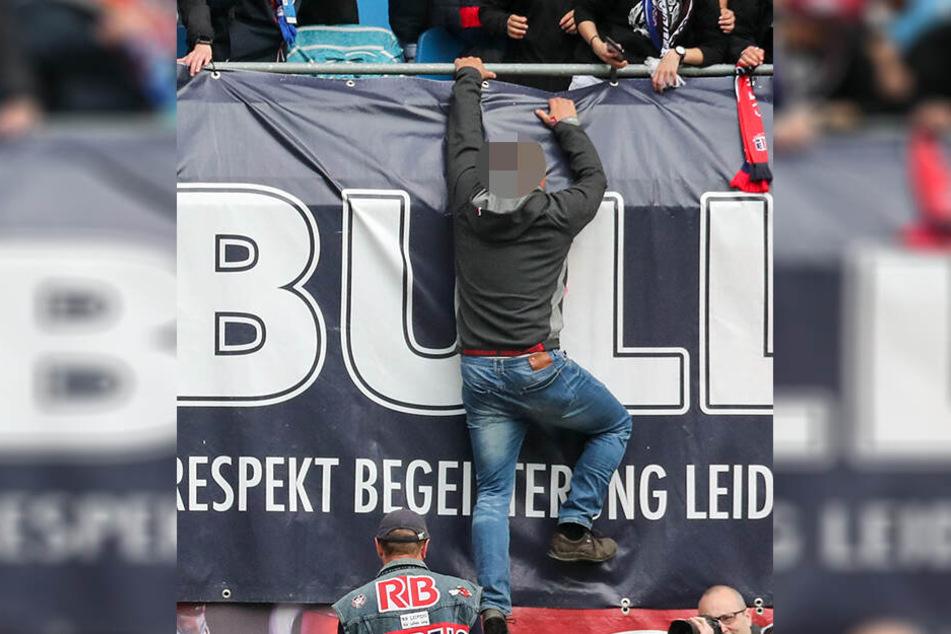 Nach dem Abpfiff kletterte ein RB-Fan über die Brüstung und sprang in die Tiefe. Unten wartet Ralf Rangnick in seiner Weste, mit dem der Anhänger ein Foto machen will.