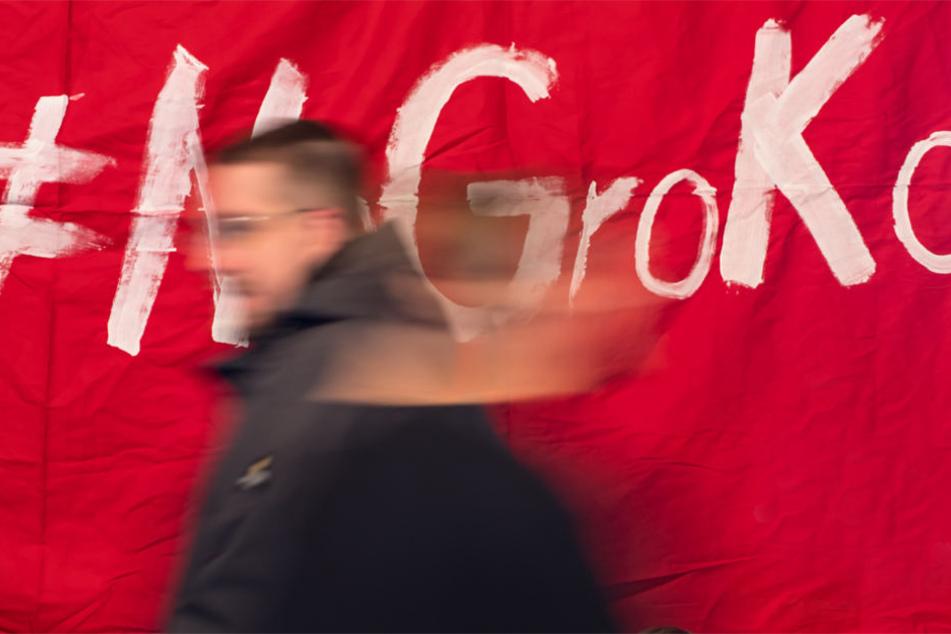 """Politisch Interessierte laufen bei einer Veranstaltung """"Groko oder NoGroko"""" vor einem Plakat mit der Aufschrift """"#NoGroKo""""."""