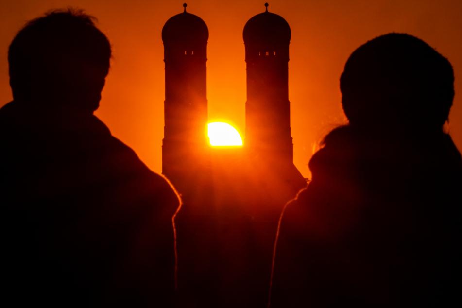 Ein Pärchen schaut der Sonne zu, die hinter der Frauenkirche mit ihren beiden 99 Meter hohen Türmen im Herzen der bayerischen Landeshauptstadt untergeht.