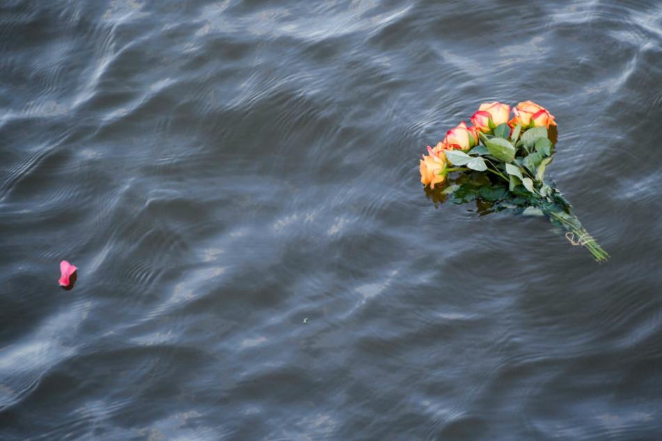 Bei einer Demonstration für Seenotrettung in Hamburg schwimmt ein Blumenstrauß im Wasser.