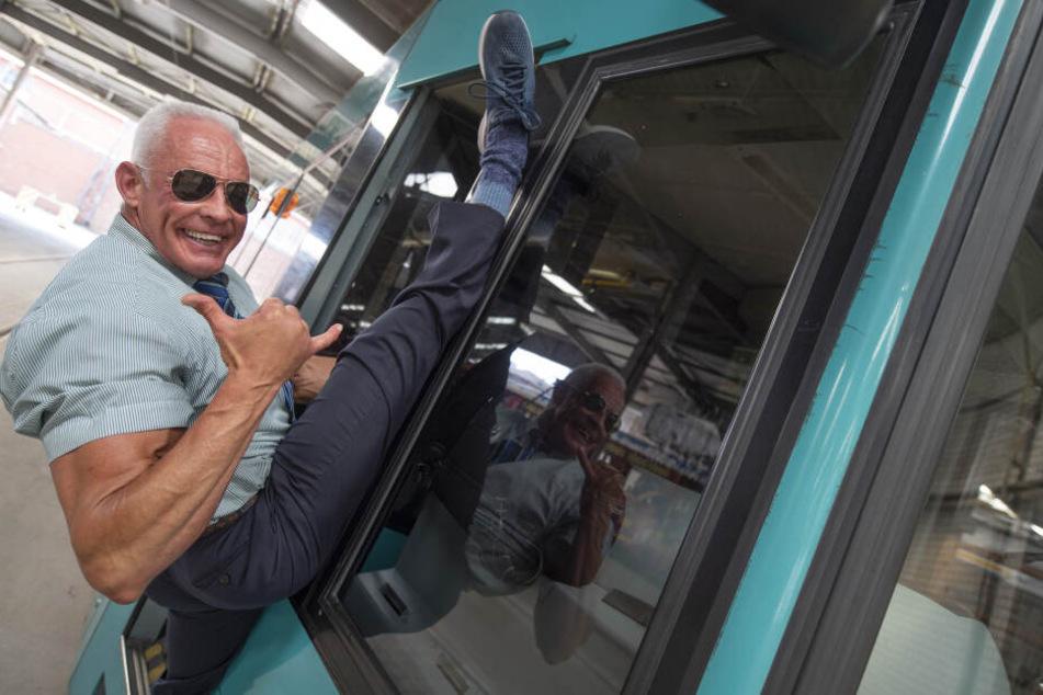 Peter Wirth (57) stretcht sich an einer Straßenbahn.