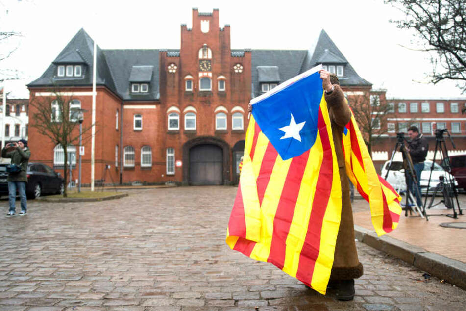Eine Frau stand vor der JVA Neumünster in eine Estelada Blava, die Fahne der katalanischen Nationalisten. Der frühere katalanische Regionalpräsident Puigdemont befand zu der Zeit in Neumünster in Gewahrsam.