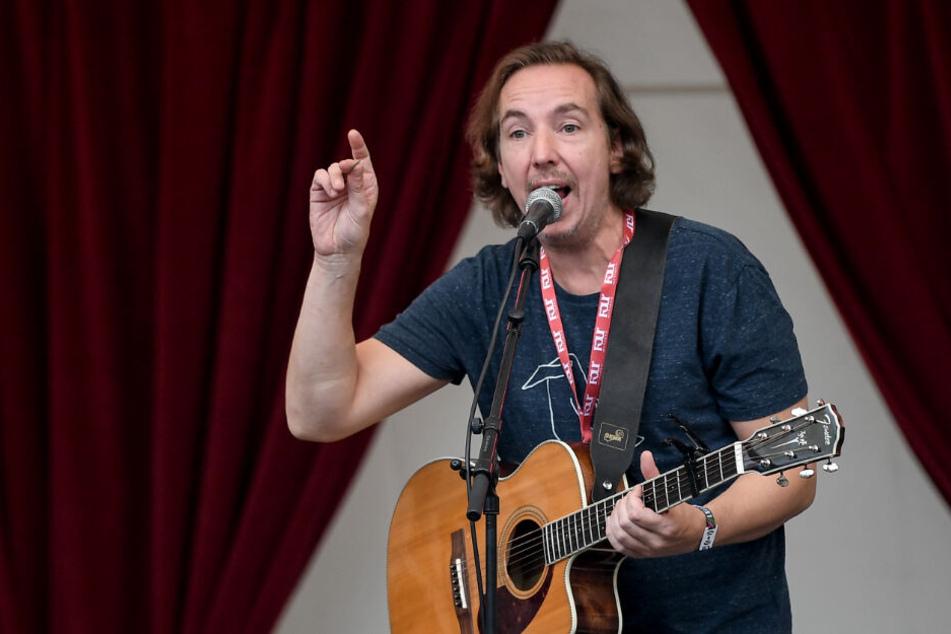 Der Musiker Olli Schulz steht bei einem Auftritt auf der Bühne.