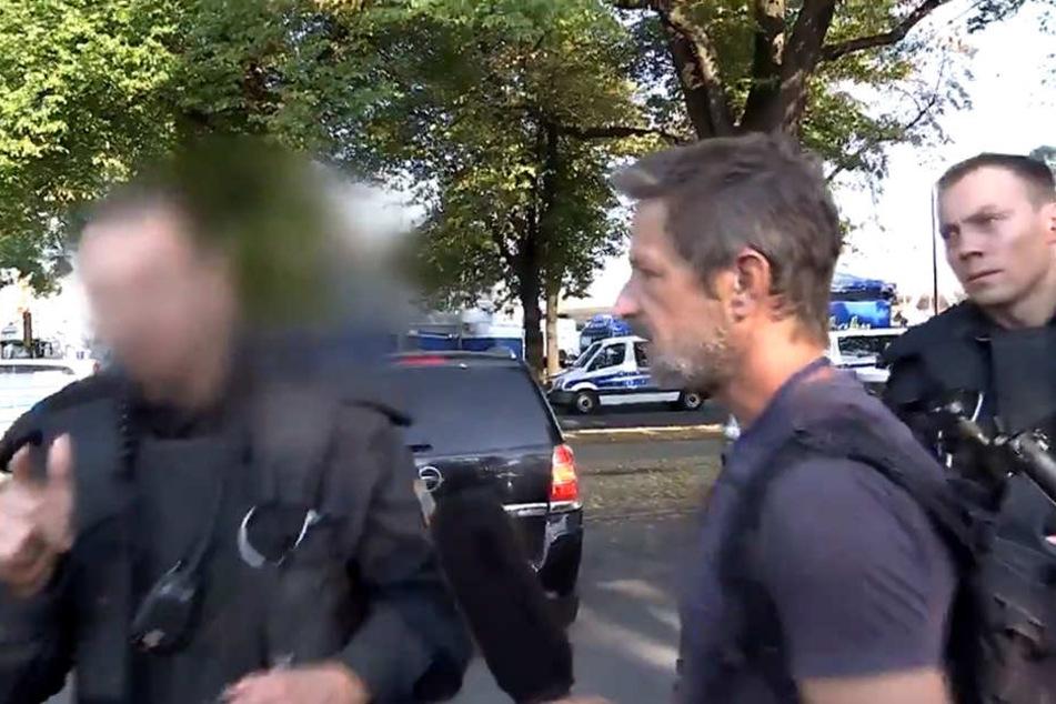 Darum geht es: Polizisten stellen die Personalien von TV-Reporter Arndt Ginzel (r.) fest. Vorher war ein Kameramann Ginzels von einem Demonstranten zur Polizei gedrängt worden.