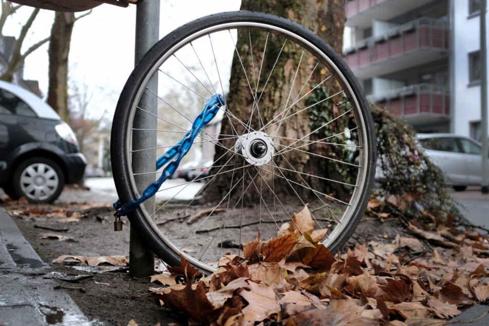 Das Laufrad eines Fahrrades steht angekettet an einem Laternenmast in Dinslaken (Nrw).