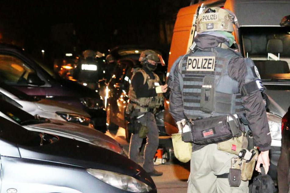 Zwei Beamte stehen zwischen geparkten Autos.