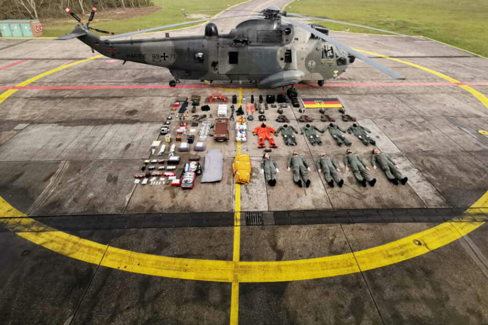 Stillgelegen! Fünf Seenotretter samt Ausrüstung liegen neben einem Rettungshelikopter SeaKing MK41.