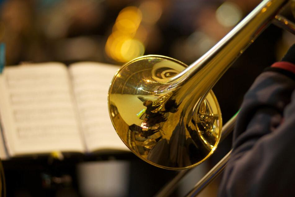 Eine Trompeter spielt vor einem Notenbuch.