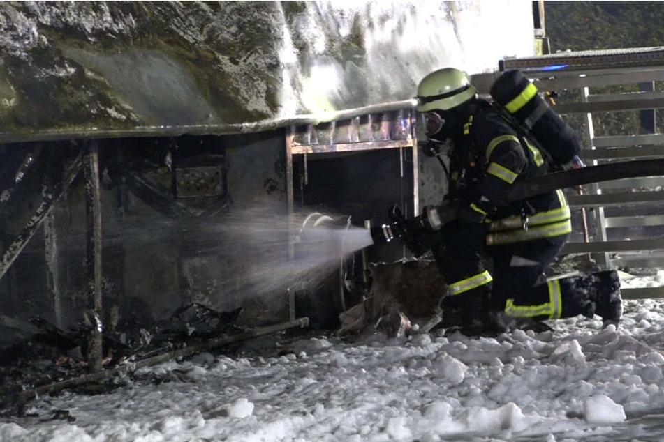 Ein Feuerwehrmann löscht den Bus.