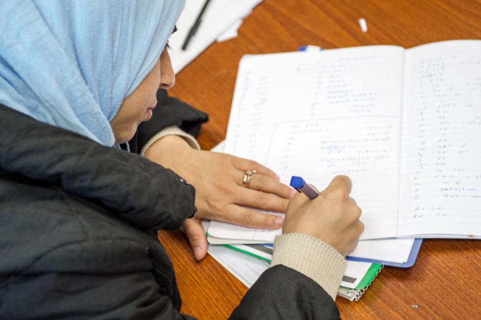 Eine nach Deutschland geflohene Frau nimmt in Frankfurt am Deutschunterricht teil (Archivbild).