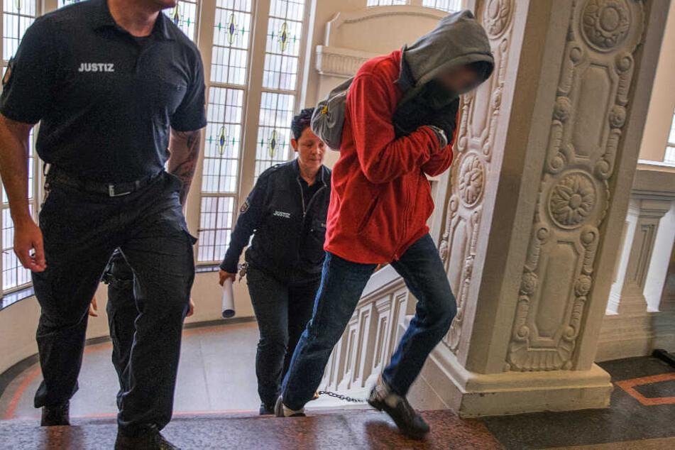 Der Angeklagte betritt in Begleitung von zwei Justiz-Beamten das Gericht.