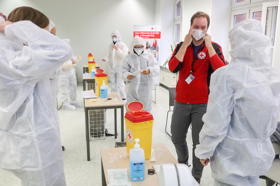 Dozent Jascha Gionkar (2.v.r.) erläutert den Teilnehmer eines Kurses für das Anwenden von Antigen-Schnelltest auf SARS-VoV-2 das Anlegen der Schutzausrüstung. Das Deutsche Rote Kreuz bildet nun Corona-Schnelltester aus.