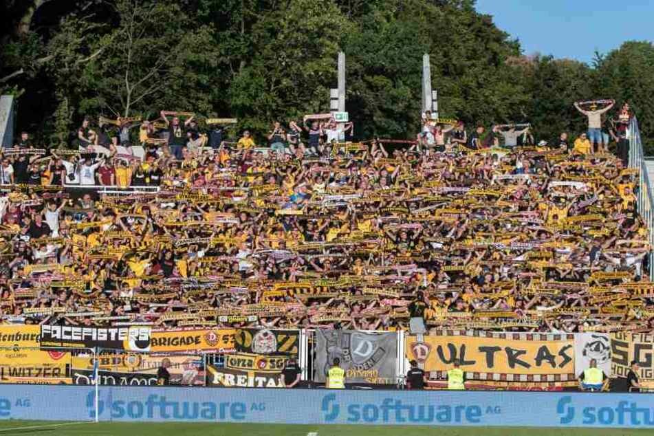 Die Fankurve beim Spiel von Dynamo in Darmstadt. Man sieht im Hintergrund, dass einige Fans auf der Mauer sitzen und stehen.