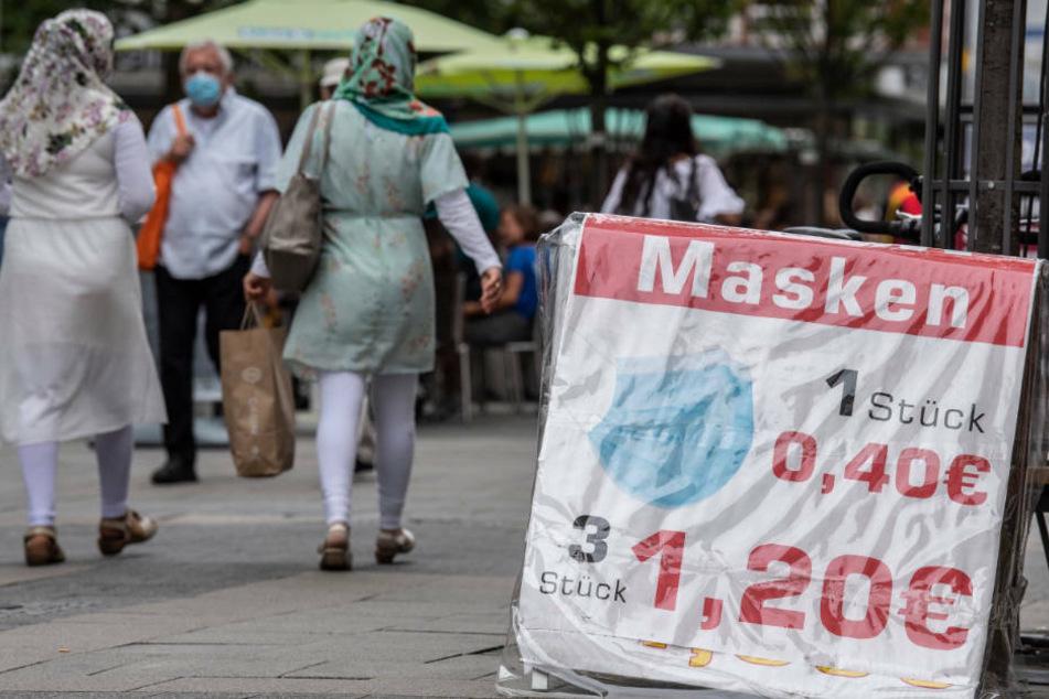 Auf ein Masken-Sonderangebot macht ein Schild in der Fußgängerzone von Offenbach aufmerksam. Die Stadt hat momentan mit Besorgnis erregenden Zahlen von Corona-Neuinfektionen zu kämpfen.