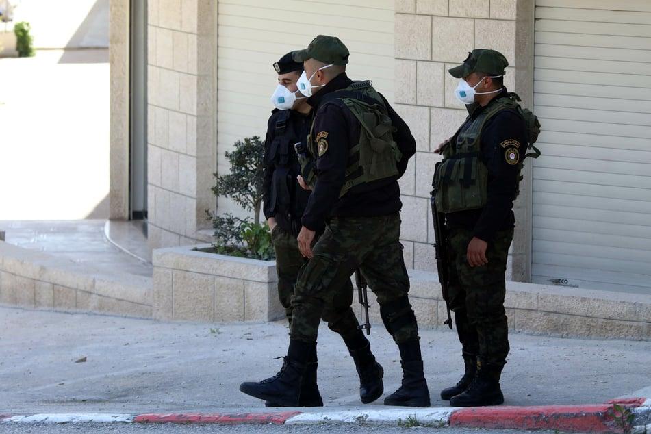 Bethlehem: Palästinensische Polizisten mit Mundschutzmasken kontrollieren den Grenzbereich eines abgesperrten Gebietes. (Archivbild)