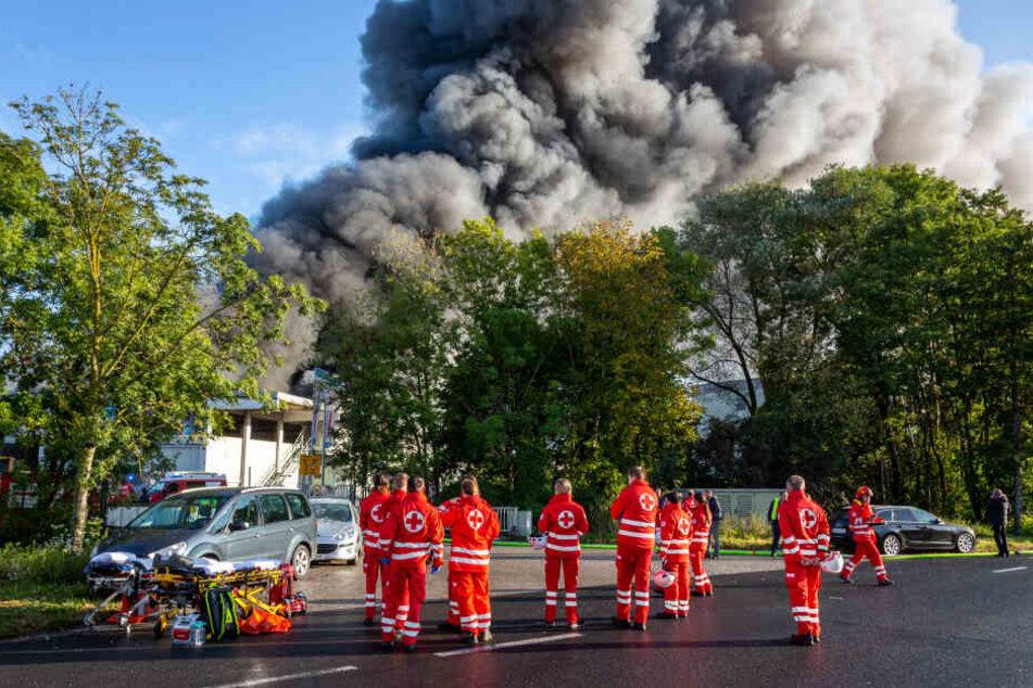 Rettungskräfte stehen bereit vor der in Brand stehenden Anlage