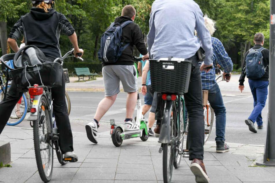 Ein E-Scooter-Fahrer im Straßenverkehr einer Großstadt.