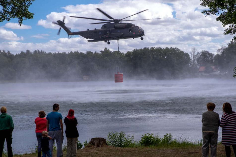 Hubschrauber fliegen mit einer großen Wasserladung Richtung Waldbrand. Schaulustige gucken gespannt zu.
