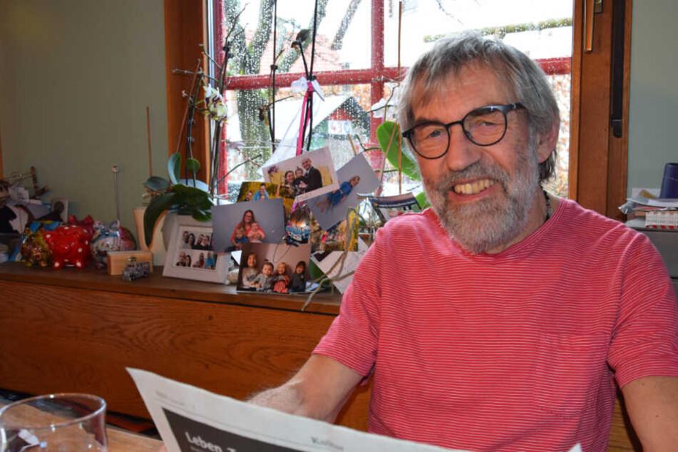Eberhard Lieb liest Zeitung, im Hintergrund Familienbilder.