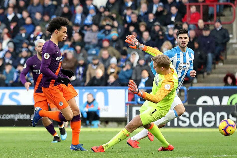 Traf am Sonntag gegen Huddersfield Town zum 3:0-Endstand: Leroy Sané setzt sich hier gegen Torwart Jonas Lössl (M.) und den Deutschen Christopher Schindler (r.) durch.
