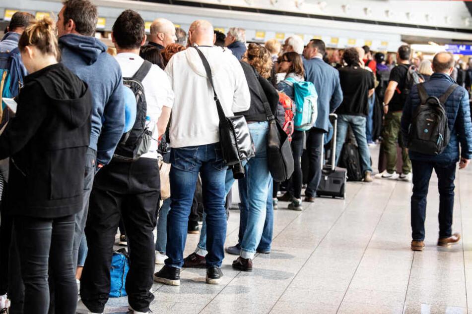 Nach der Annullierung zahlreicher Flüge warten Passagiere im Terminal 1 des Flughafens auf ihre Abfertigung.