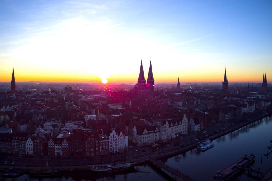 Die Sonne geht über die Hansestadt, der Stadt der sieben Türme, auf: Kirche St. Jakobi (v.l), Marienkirche, die drei Spitzen des Rathauses, St.-Aegidien-Kirche, Petrikirche und der Dom zu Lübeck. Im Vordergrund fließt die Trave.