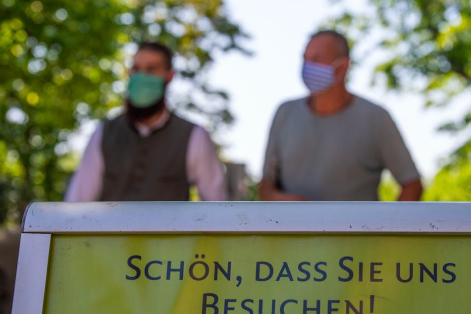 """Biergartenbesucher gehen hinter einem Schild mit der Aufschrift """"Schön, dass Sie uns besuchen!"""" her."""