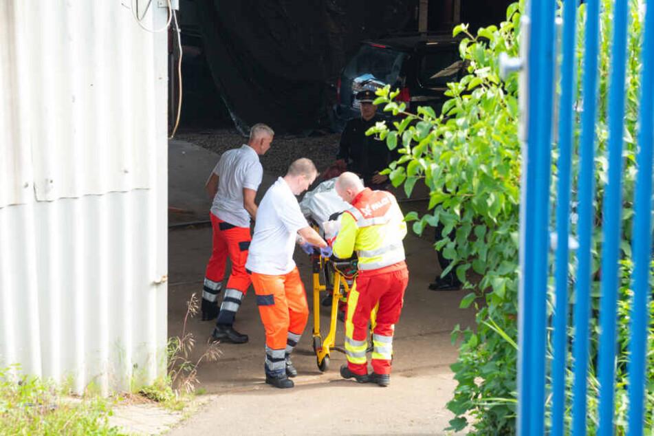 Rettungskräfte bringen die Leiche ins Institut für Rechtsmedizin.
