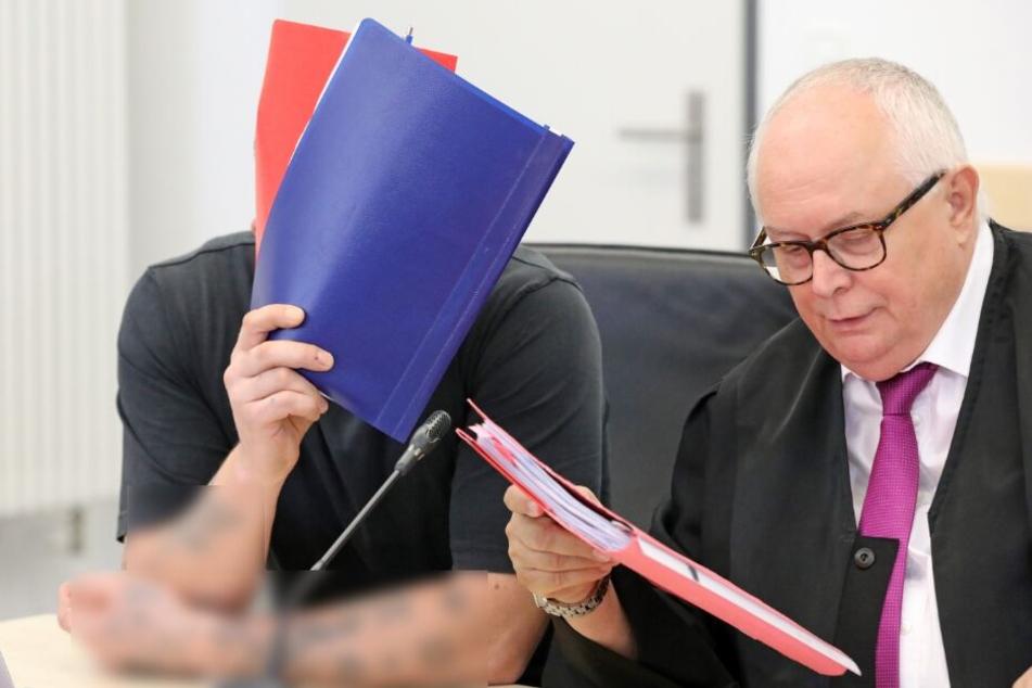 Einer der beiden Angeklagten (l) unterhält sich mit seinem Verteidiger Edgar Breitsprecher im Saal des Landgerichts.