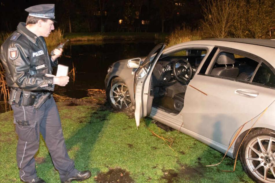 Nachdem der Mietwagen an Land gezogen wurde, nimmt ihn die Polizei genauer unter die Lupe.