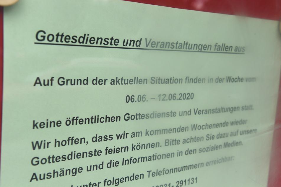 """Ein Schild mit dem Schriftzug """"Gottesdienste und Veranstaltungen Fallen aus"""" hängt in einem Schaukasten an der Pfarrkirche Heilige Dreifaltigkeit der Pfarrei St. Bernhard Stralsund-Rügen-Demmin."""