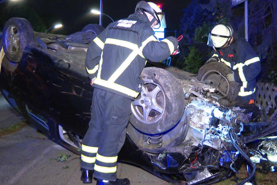Feuerwehrleute begutachten das zerstörte Auto.
