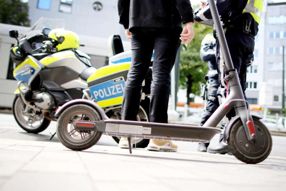 Polizisten kontrollieren in der Innenstadt von Düsseldorf einen E-Scooter-Fahrer.