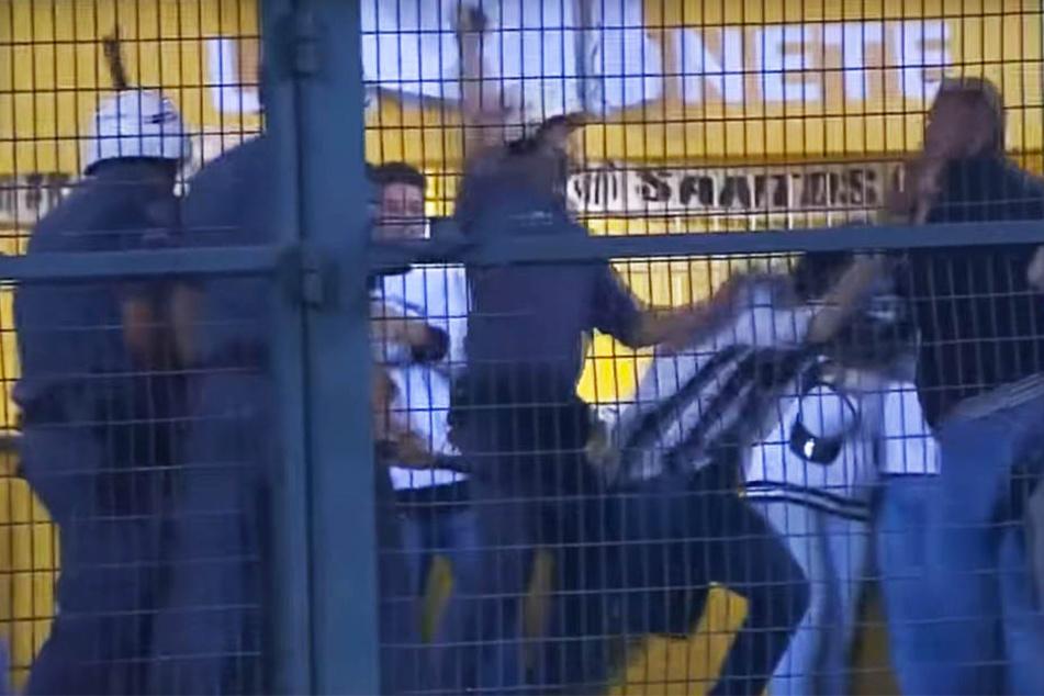 Polizisten dreschen auf Santos-Anhänger ein.