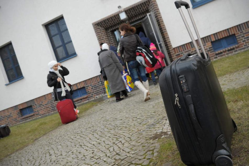 Flüchtlinge vor einer neuen Flüchtlingsunterkunft. In Ludwigsburg soll es bald Würfelgebäude, sogenannte Cubes, geben. (Symbolbild)