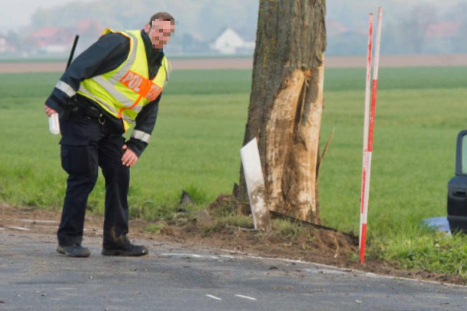 Ein Polizist beim Vermessen der Unfallstelle an dem Baum gegen den das Auto prallte. (Symbolbild)