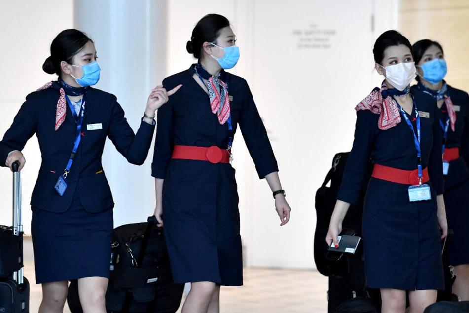 Mitarbeiterinnen der China Eastern Airlines tragen zur Uniform einen Mundschutz.