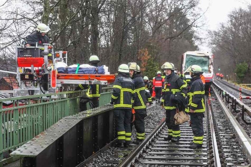 Feuerwehrleute transportieren eine Trage mit einem Verletzten ab.