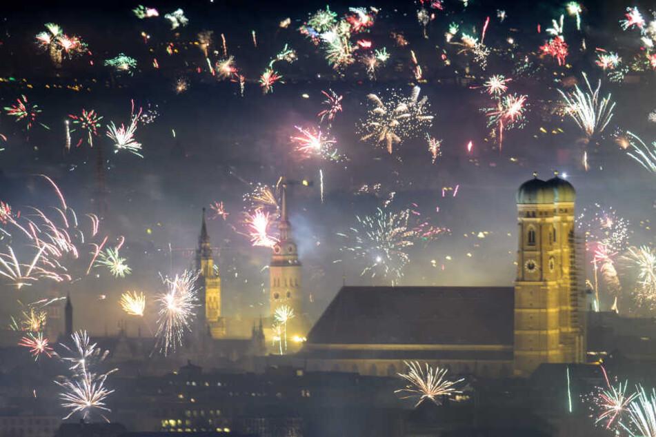 Feuerwerksraketen explodieren in der Silvesternacht über der Frauenkirche und der Innenstadt in München.